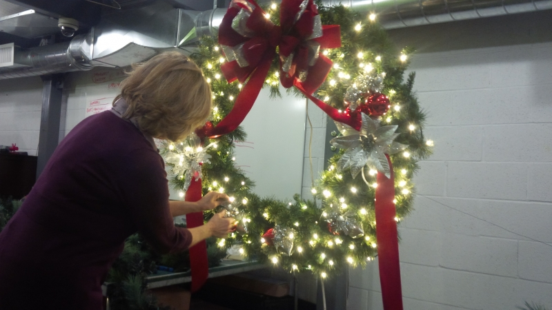 Pro Decorators in LawnSavers office carefully crafting a custom Christmas wreath for a client
