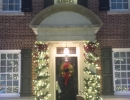 Elegant Lit Garland wrapped pillars with bows at front entrance